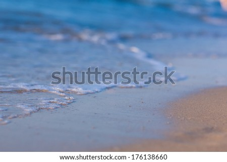 Soft wave of the sea on the sandy beach background - stock photo