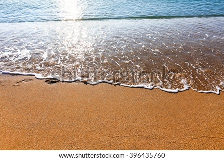 Soft wave of the sea washing foot marks from the sandy beach - stock photo