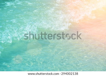 Soft wave of the turquoise sea on the sandy beach. Natural summer background with copy space - stock photo