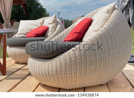 Soft wicker armchairs with color pillows outdoors. Horizontal shot - stock photo