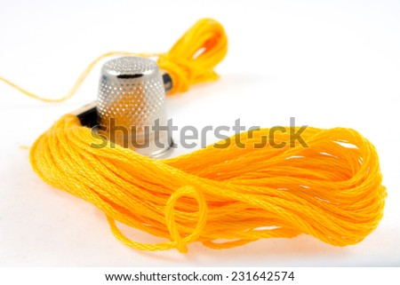 soft yellow cotton thread and a thimble - stock photo