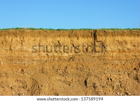 Soil cross section, green grass and blue sky - stock photo