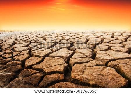 Soil drought cracked landscape sunset - stock photo