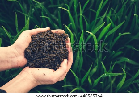 Soil in hand, palm, cultivated dirt, earth, ground, brown land background. Organic gardening, agriculture. Nature closeup. Environmental texture, pattern. Mud on field. - stock photo