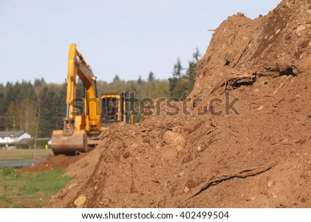 Soil or dirt in the foreground with an industrial shovel in the background/Heavy Lifters and Moving Earth/An industrial shovel a pile of dirt.  - stock photo