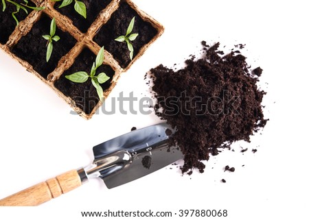 soil, shovel and  seedling in peat pots isolated on white background. top view