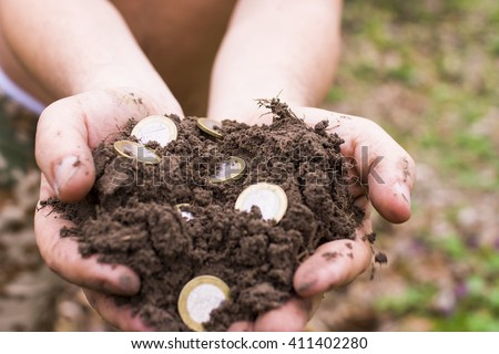 Soil with coins in a human hand