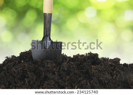 Soil with shovel and green bokeh - stock photo