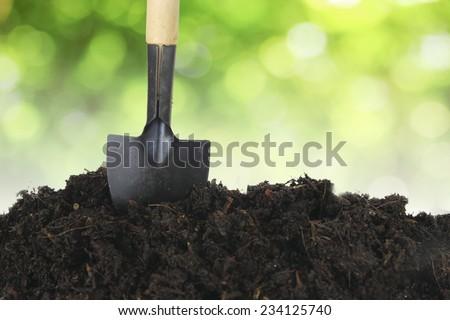 Soil with shovel and green bokeh - stock photo