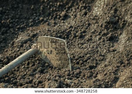 Soil with shovel. Close-up, shallow DOF. - stock photo