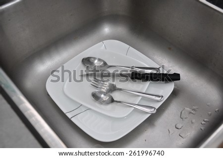 Soiled plates and utensils in sink - stock photo