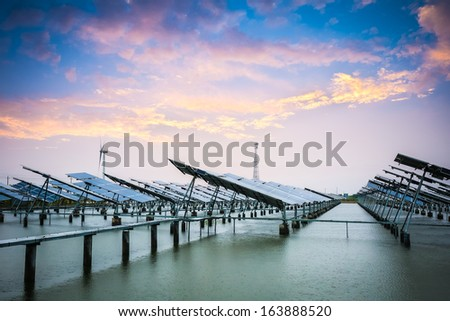 solar and wind power in sunset,green energy background. - stock photo