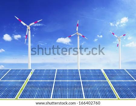 solar cells and wind turbine on blue sky - stock photo