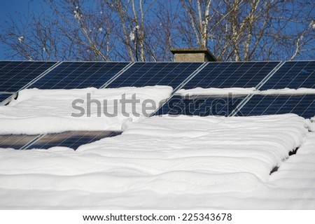 solar cells on a snowy roof - stock photo