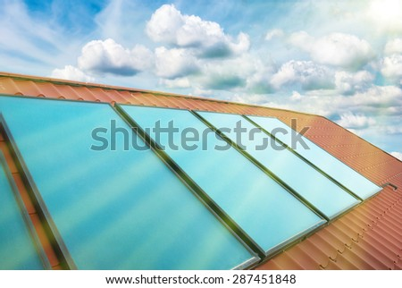 Solar cells on the red house roof under shining sun, blue sky with clouds - stock photo