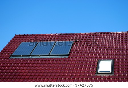 solar collectors ont the house roof for warm water supply - stock photo