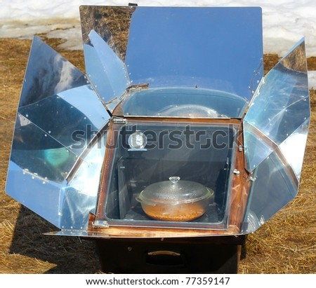Solar cooking with a solar oven on a sunny day - stock photo