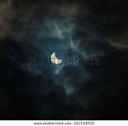 solar eclipse on a dark background of clouds. Sun closes the moon during the day we see it Event overseen by a lot of people. - stock photo