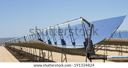 solar electric power plant parabolic mirrors concentrating sunlight - stock photo