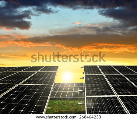 Solar energy panels against sunset sky - stock photo