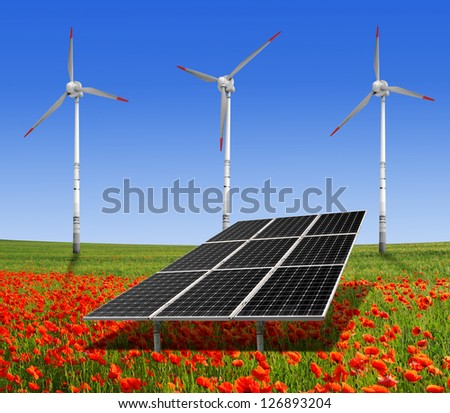 solar energy panels and wind turbine on the poppy field - stock photo