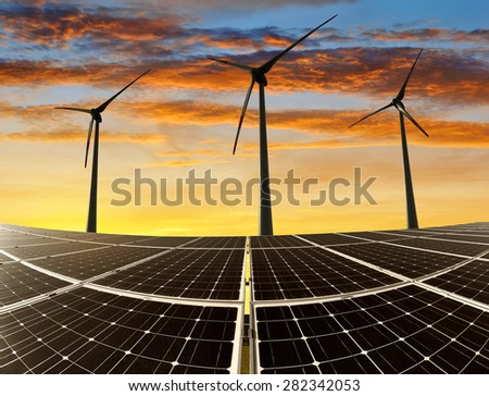 solar energy panels and wind turbines in the sunset