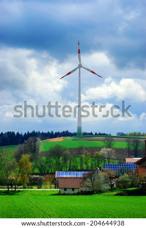 solar energy panels at the countryside house and wind turbine in field  - stock photo