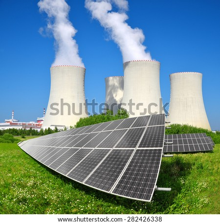 Solar energy panels before a nuclear power plant - stock photo