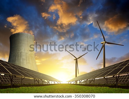Solar energy panels, wind turbines and nuclear power plant at sunset. - stock photo