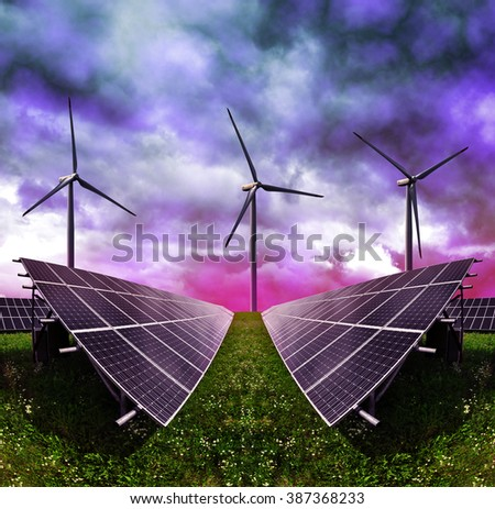Solar energy panels with wind turbines against storm clouds. Clean energy.