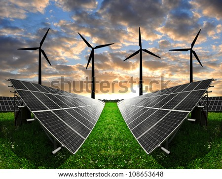 Solar energy panels with wind turbines in the sunset