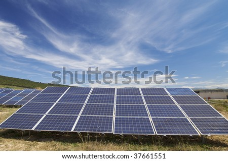 solar field with cloudy sky - stock photo