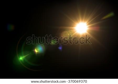 Solar lens flare on black background - stock photo