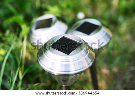 solar lights on a green glade in the afternoon, charged by the sun - stock photo