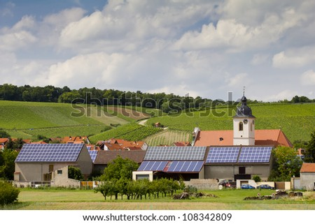 Solar mirrors installed on the roofs of a small village with church and farmhouses in Franconia, Bavaria (Germany).