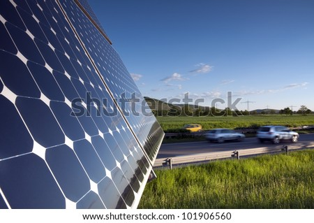 Solar Panel Against Blue Sky With Green Landscape And Highway - stock photo