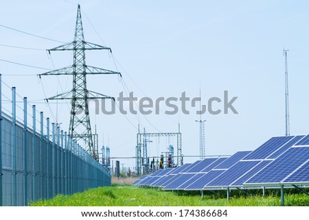 solar panel against high voltage tower  - stock photo