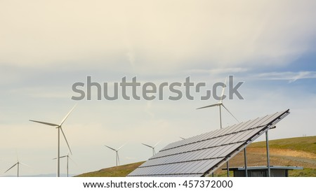 Solar panel and row of wind turbines under cloud blue sky at Ellensburg, Washington, US. Power plant generates renewable energy from sun and wind. Clean, sustainable power concept. Panorama style. - stock photo