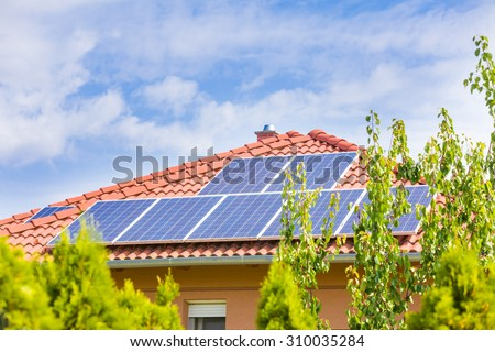 Solar panel cells on the roof of a new house against blue sky. - stock photo