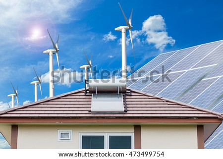 Solar panel for hot water system on roof and wind turbines blue sky background , Energy saving and natural energy concept