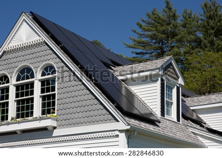 Solar panel installation on a nice cape cod house with sunny blue skies in the background - stock photo