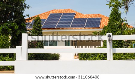 Solar panel on a orange roof reflecting the sun and the cloudless blue sky - stock photo