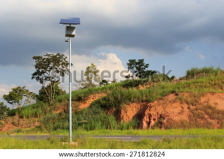 Solar panel on electric pole for lightning on road in countryside with rainy clouds on sky, use of Solar energy, Rio de Janeiro, Brazil - stock photo