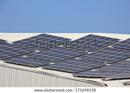 Solar panel on  roof reflecting the sun and the cloudless blue sky