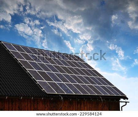 Solar panel on the roof of the house at sunset - stock photo