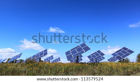 Solar panel power generator field under sunny blue sky, with beautiful wild autumn landscape - stock photo