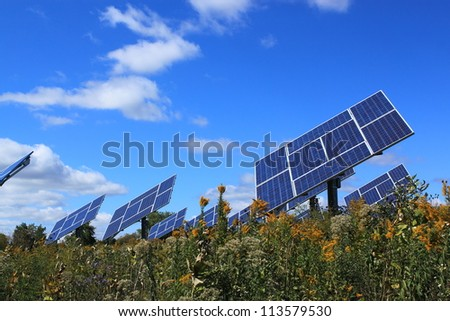 Solar panel power generator field under sunny blue sky, with beautiful wild autumn landscape - stock photo