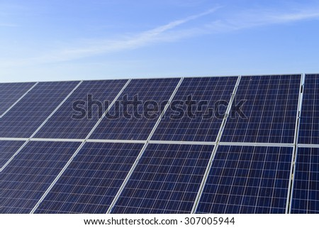 Solar panel produces green, environmentally friendly energy from the sun with blue sky - stock photo