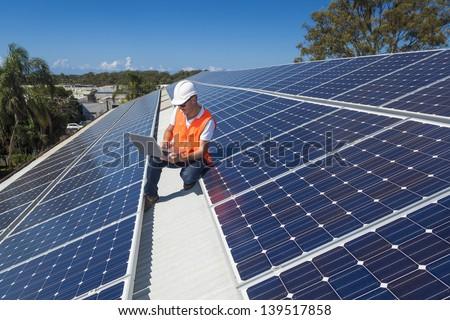 Solar panel technician on roof - stock photo