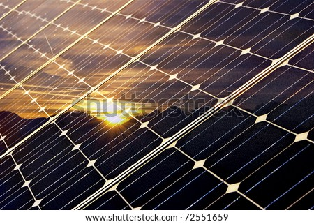 solar panel with mountains and setting sun, green economy - stock photo